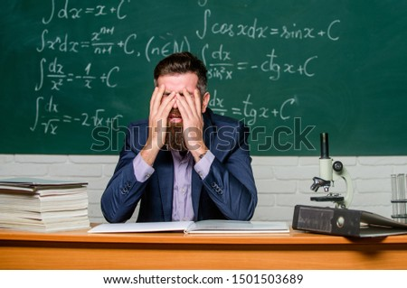 Teaching dumb students. Difficult work. Emotional burnout. Teacher give up. Hate his job. Teacher mature man. Fed up. Man desperate teacher in classroom. No hope for better. Tired and exhausted.