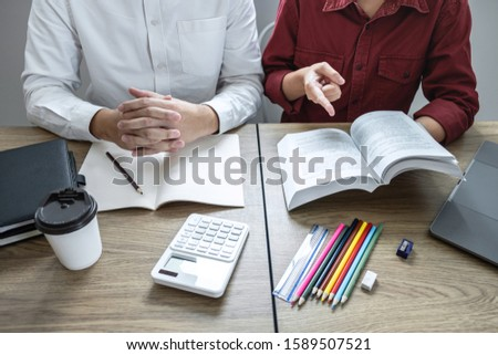 Teaching helping and study course, Team of young teacher or tutor helps students to learning in classroom for homework a test or exam at desk with papers.