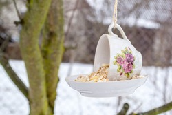 Teacup bird feeder made from a vintage cup and saucer glued together. Teacup bird feeder hanging on a tree.