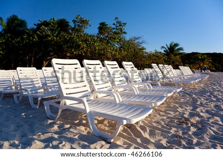 Teak chairs and palms in the beach