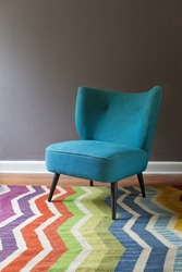 Teal blue retro armchair and colorful chevron pattern rug interior with grey wall