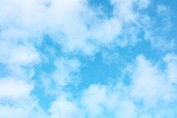 Teal blue sky with puffy clouds, an abstract background