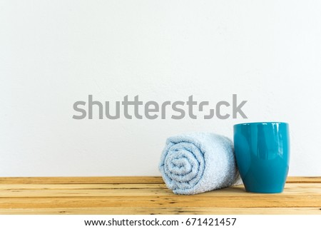 teal color coffee cup and cyan towel on wooden table with white cement wall background #671421457