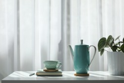Teal cup and tall teapot with notebook and silver pen on white table with plant pot in front of a see-through curtain
