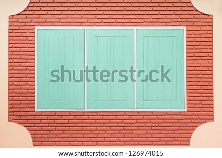 Teal rectangular wooden window on bare brick wall