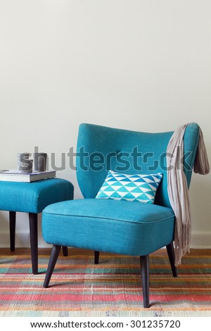 Teal retro armchair and colorful pink pattern rug interior with ottoman