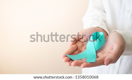 Teal ribbon awareness on female hands in white t-shirt. Symbolic for cervical cancer, ovarian cancer, gynecological cancer and PCOS. Women's health care concept. Copy space.