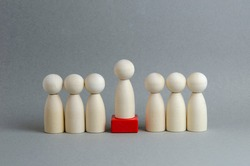 Team and leader on a pedestal on a gray background. Wooden figures in the image of people. Chief at work, leadership and personnel management, business concept.