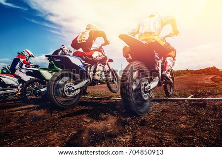 Team athletes on mountain motorcycles on motocross. Sun of light
