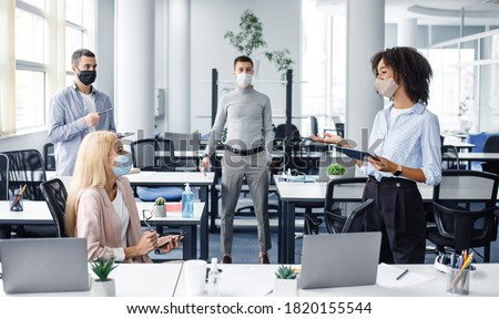 Team building and teamwork during meeting. African american woman manager with tablet in hand gives tasks to workers in protective mask keeping social distance in interior of modern office, panorama