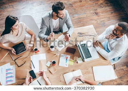 Team communication. Top view part of group of five people discussing something with smile while sitting at the office table