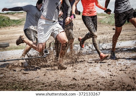Team competition with an obstacle. Finish team in a big mud puddle. Close-up #372133267