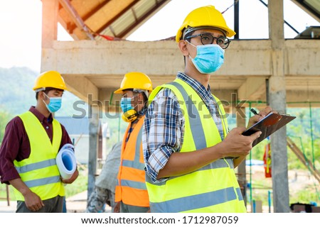 Team engineers and  builders having wearing protective masks to prevent dust and covid 19 disease during the inspection in construction site,Coronavirus has turned into a global emergency.