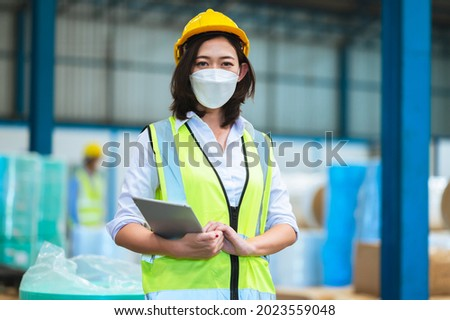 Team engineers and foreman wear a mask, hard hat, and vest. Standing consult discuss industrial production management. Explaining job details through laptops and tablets in factories or warehouses. Photo stock ©