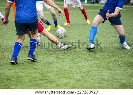 Team fight for ball in football match. Soccer player legs in action