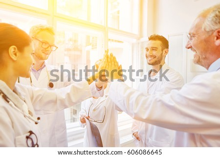 Team giving High Five during medical meeting as motivation