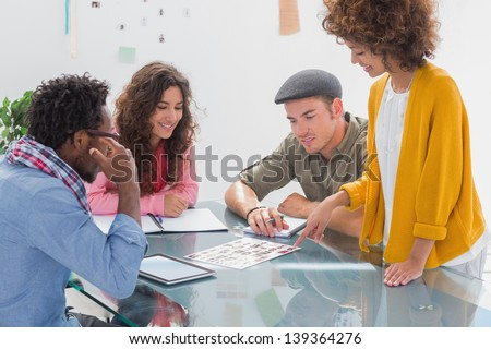 Team going over photo contact sheet at desk during meeting