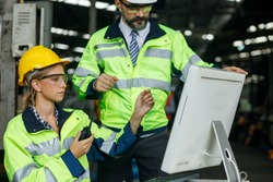 Team Industrial engineer work on personal computer She designs robot AI Model, Her male colleague talks with her and uses computer. Inside the Heavy Industry Factory.