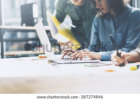 Team job. Photo young businessmans crew working with new startup project in modern loft. Generic design notebook on wood table. Horizontal, film effect #387274846