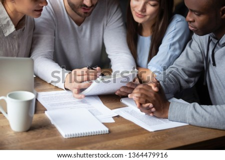 Team leader hold notebook pen explaining talking with associates cropped close up image, diverse students girls and guys sitting together at table studying preparing to test. Teamwork support concept #1364479916