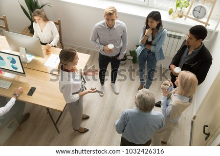 Team leaders meet multiracial interns in office explaining new job, company executives talking to diverse workers listening instructions at break, discussion and computer work in coworking, top view