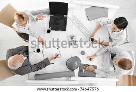 Team meeting from overhead view, businesspeople discussing work at office meeting table.?