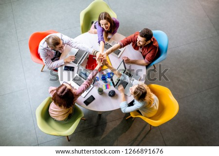 Team of a young coworkers dressed casually working together with laptops sitting at the round table in the office, view from above #1266891676