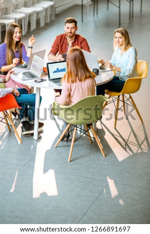 Team of a young coworkers dressed casually working together with laptops sitting at the round table in the office