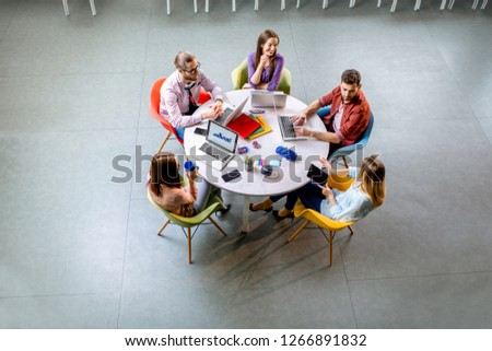 Team of a young coworkers dressed casually working together with laptops sitting at the round table in the office, view from above