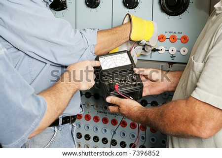Team of actual electricians testing the voltage on an industrial power distribution center. All work is being performed according to industry code and safety standards.