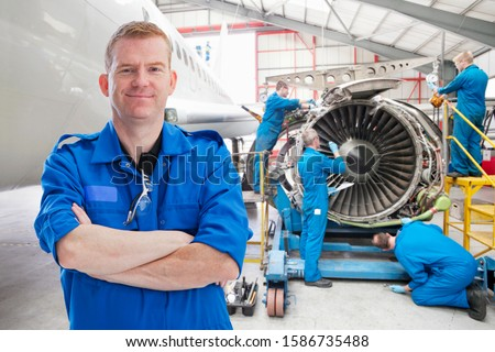 Team Of Aero Engineers Working On Aircraft In Hangar