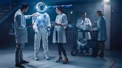 Team of Aerospace Engineers Design New Space Suit Adapted for Galaxy Exploration and Travel. Group of Scientists Wearing White Coats have Discussion, Use Computers. Constructing Astronaut Helmet