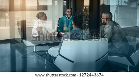 Team of african bussines people talking during an work meeting shot through a glass window, looking into the boardroom