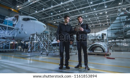 Team of Aircraft Maintenance Mechanics Moving through Hangar. Holding Tablet Computer