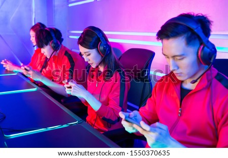 Team of asian teenage cyber sport gamers play mobile game by smartphone on eSport tournament