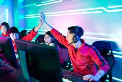 Team of asian teenage cyber sport gamers win the multiplayer PC video game on eSport tournament and give five to each other