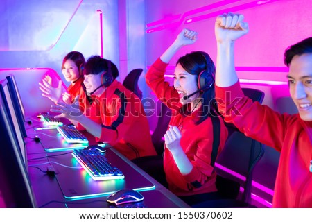Team of asian teenage cyber sport gamers win the multiplayer PC video game on eSport tournament and cheer with hand up