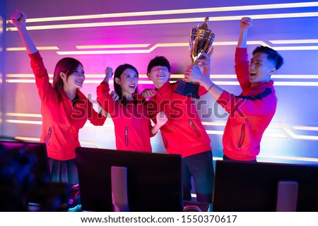 Team of asian teenage cyber sport gamers win the multiplayer PC video game on eSport tournament and get the trophy Photo stock ©