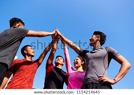 team of asian young adult sportsmen and sportswoman putting hands together to show unity and teamwork spirit. #1114214645