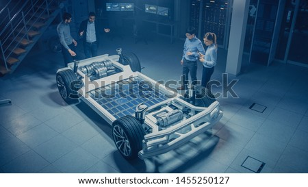 Team of Automotive Engineers Working on Electric Car Chassis Platform, Taking Measures, working with 3D CAD Software, Analysing Efficiency. Vehicle Frame with Wheels, Engine and Battery.