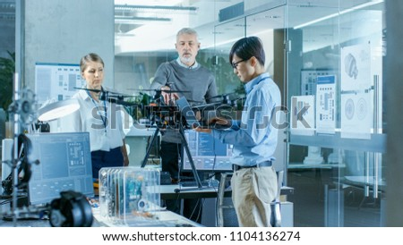 Team of Aviation Engineers Work on a New Drone, Have discussion, Use Laptops. In the Background Scientific Laboratory.