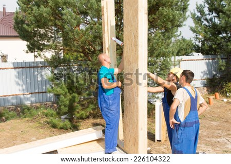 Team of builders erecting prefab wooden wall panels on the building site of a new house under construction