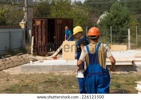 Team of builders or workmen on site at a new build house construction installing the insulated wooden wall panels