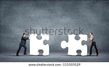Team of business people collaborate holding up jigsaw puzzle pieces as a solution to a problem
