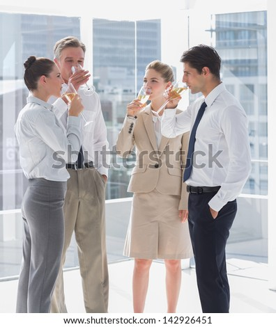 Team of business people drinking champagne in the workplace
