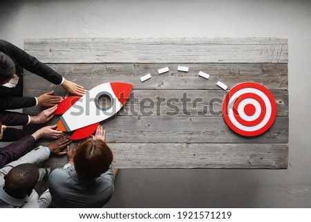 Team of business people with rocket as a sumbol of high risky goals targeting at red target at meeting table