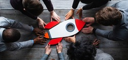 Team of business people with rocket as a sumbol of high risky goals targets success at meeting table