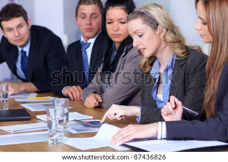 Team of 5 business people working on some calculations, calculator and come documents on conference table, focus on blonde female