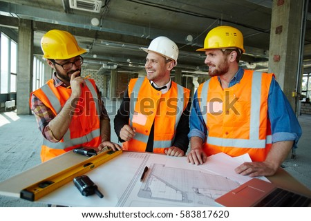 Team of cheerful construction workers discussing project details with executive supervisor standing at table with blueprints, tools and laptop on it