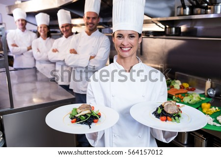 Team of chefs in the kitchen with one presenting dishes